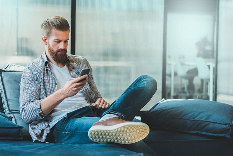 Confident bearded man is sitting on couch and typing on smartphone. He has some rest