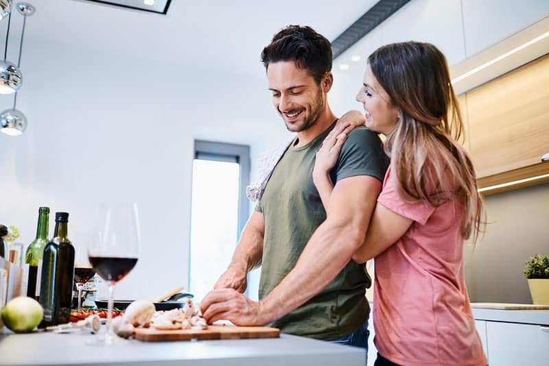 Loving joyful young couple embracing and cooking together, having fun in the kitchen