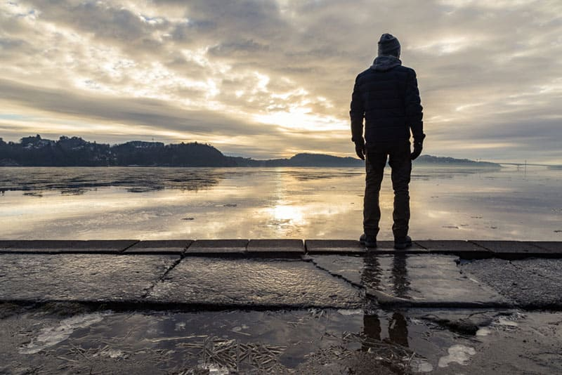 Man standing at the shore, looking at the calm sea. Reflections of the man in the ice on the ground. Mist and fog. Hamresanden, Kristiansand, Norway