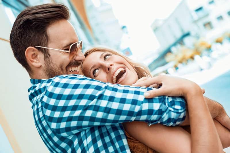 smiling man hugging woman