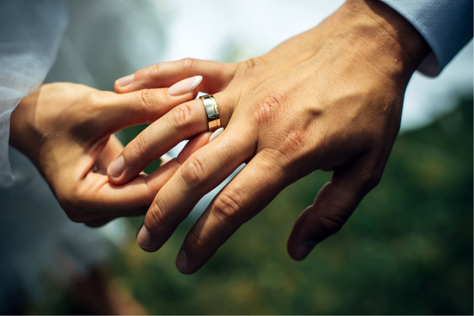 the bride puts the engagement ring on the groom's hand
