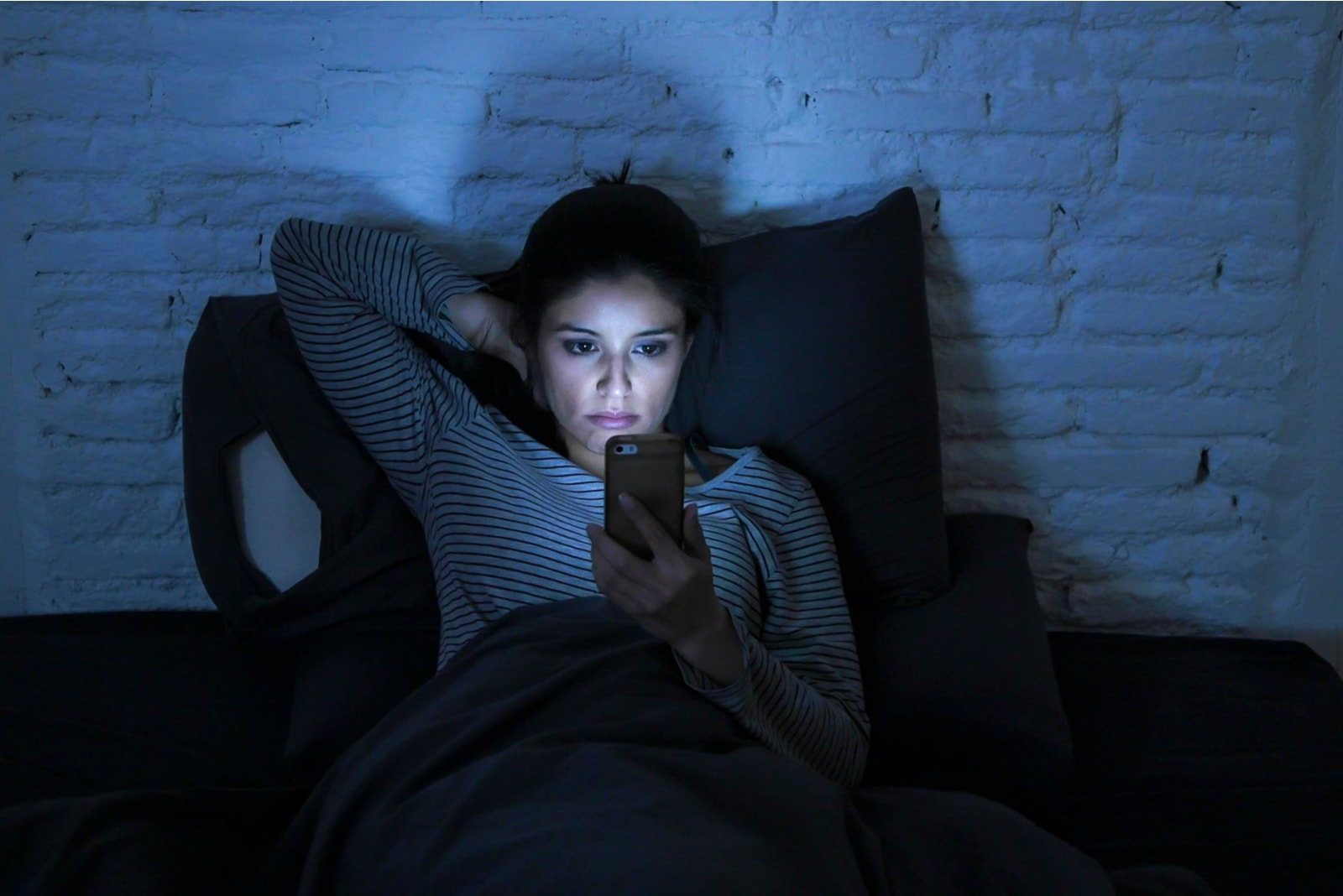 the night before bed a sad woman lies in bed and uses a smartphone