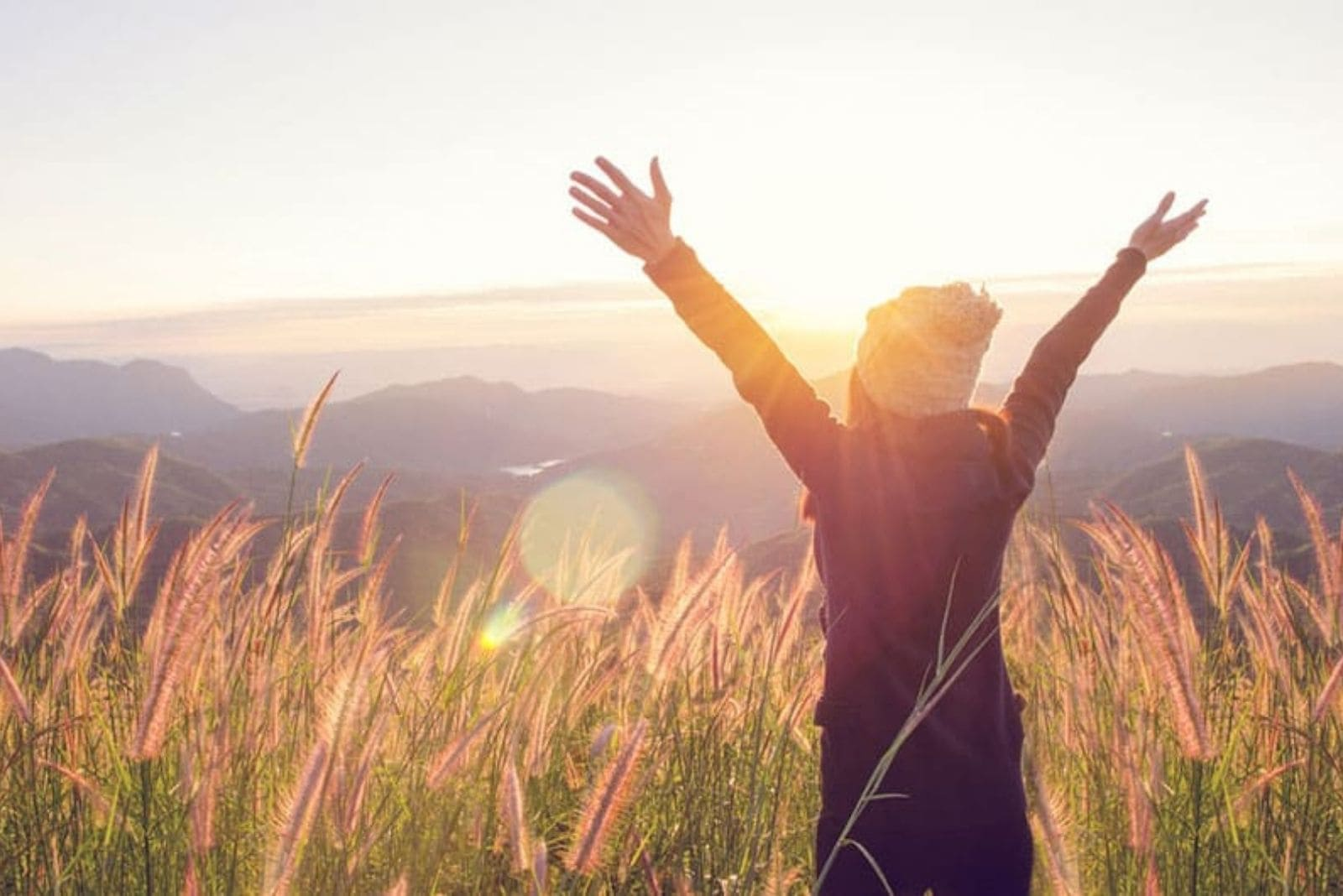the woman stands with outstretched arms in the field