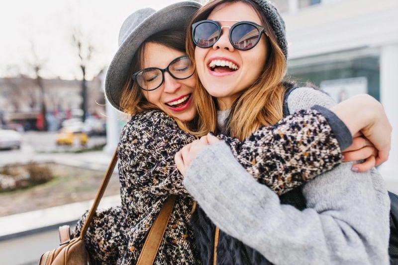 two stylish girls hugging on street
