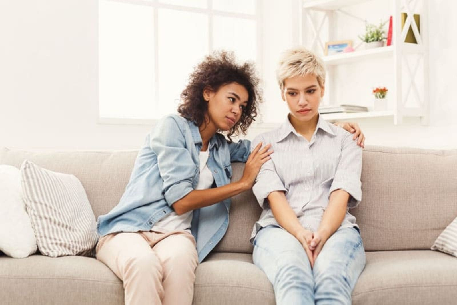 two women sit on the couch and comfort her
