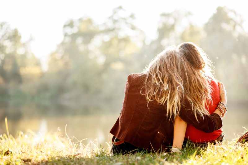 two young women sitting on grass