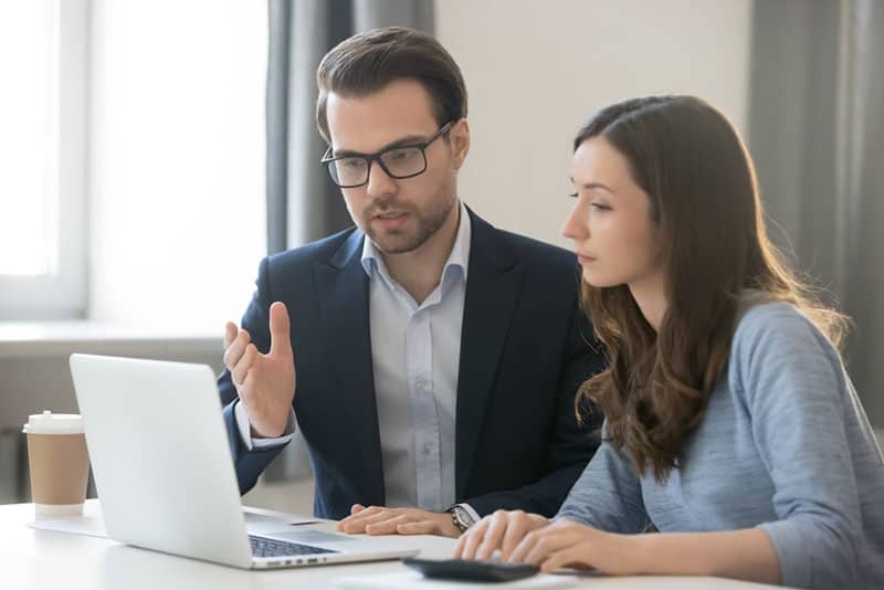 woman and man working together on laptop