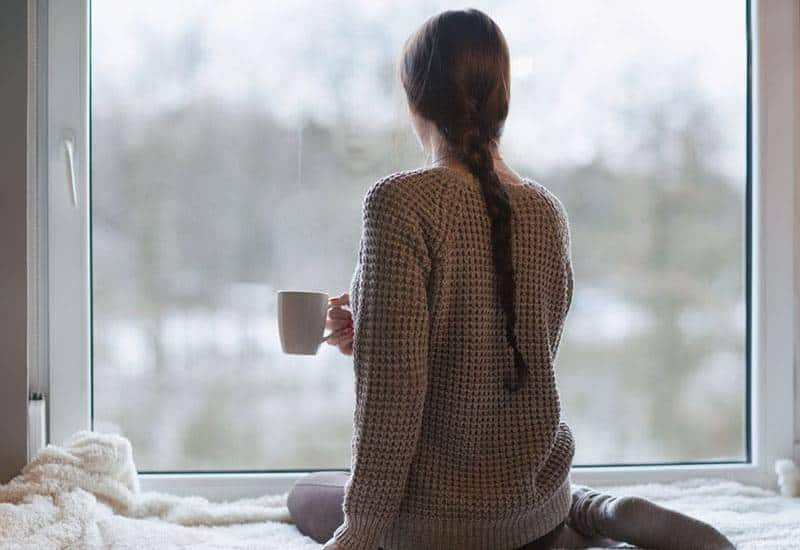 woman holding cup of tea and looking outside