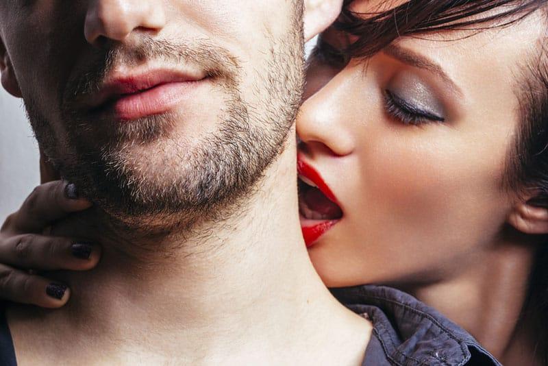 woman kissing man's neck