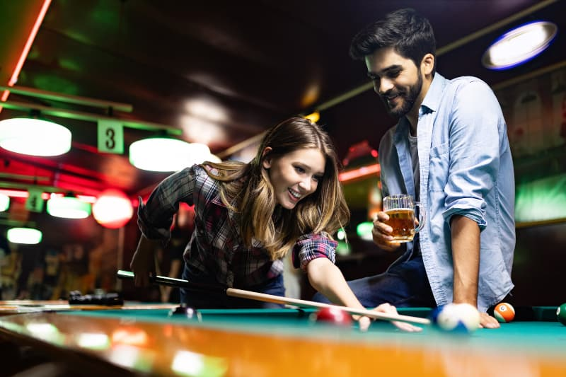 woman playing pool while smiling man looking at her with glass of beer
