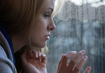 sad young blonde woman by the window looking outside
