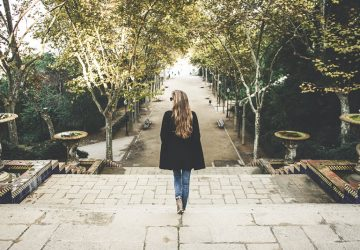 young blonde woman walking away in the park
