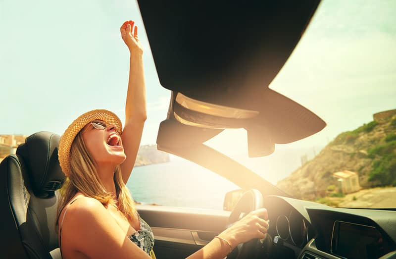 young woman driving car and laughing