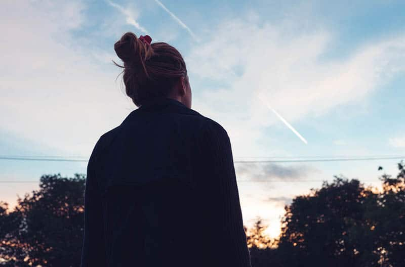 Silhouette of a young woman watching the sunset