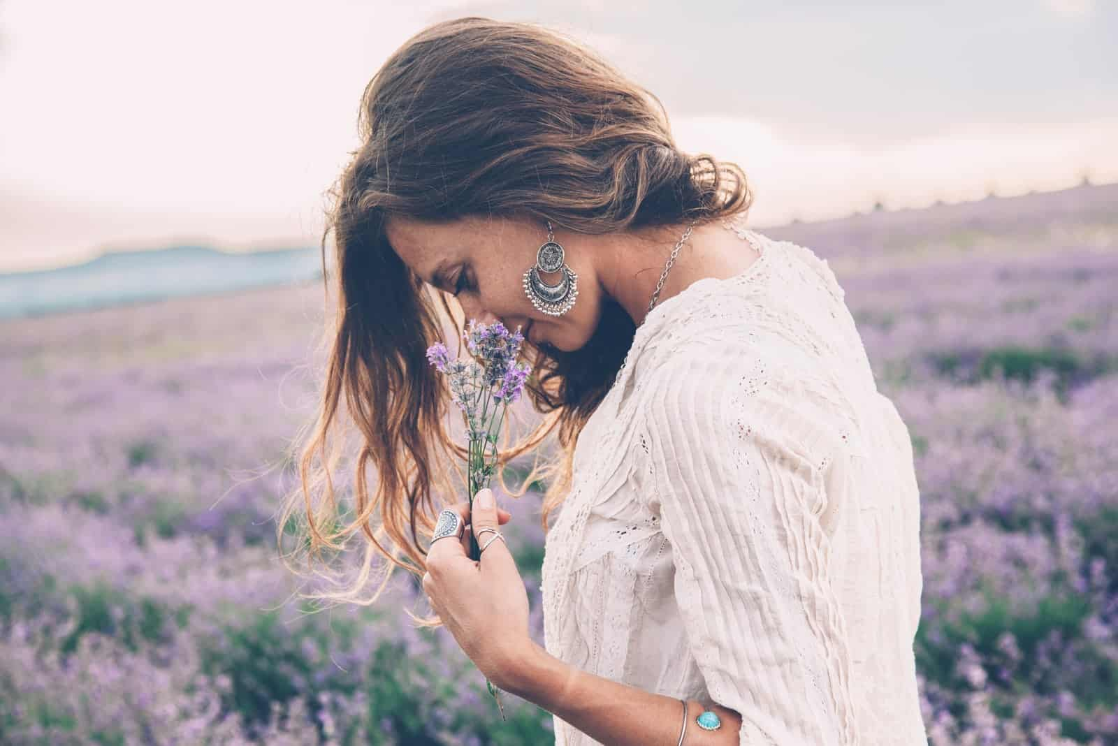 a beautiful woman walks through a lavender field and smells a lavender flower