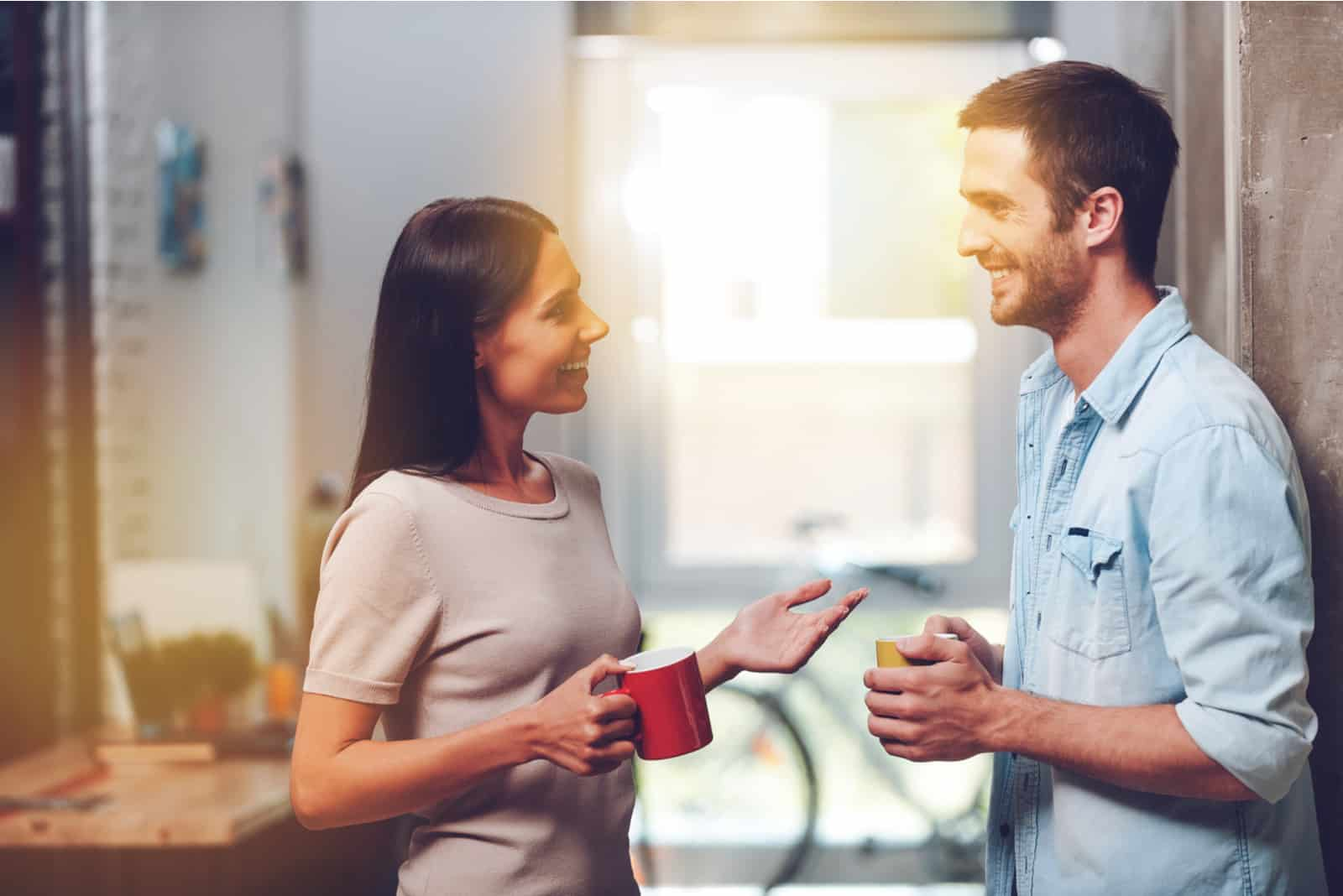 a couple in love standing holding cups in their hands and talking