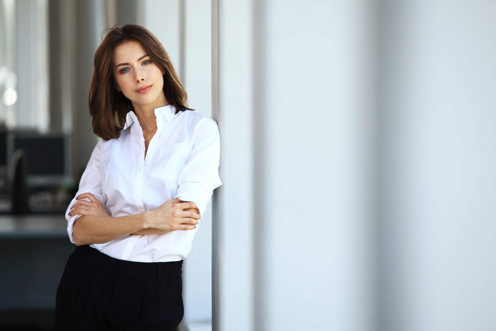 a determined woman in a white shirt stands by the window