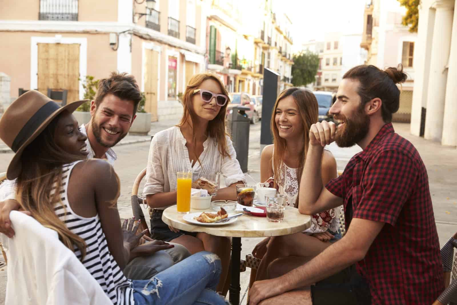 a group of smiling friends sitting on the terrace of a cafe and talking