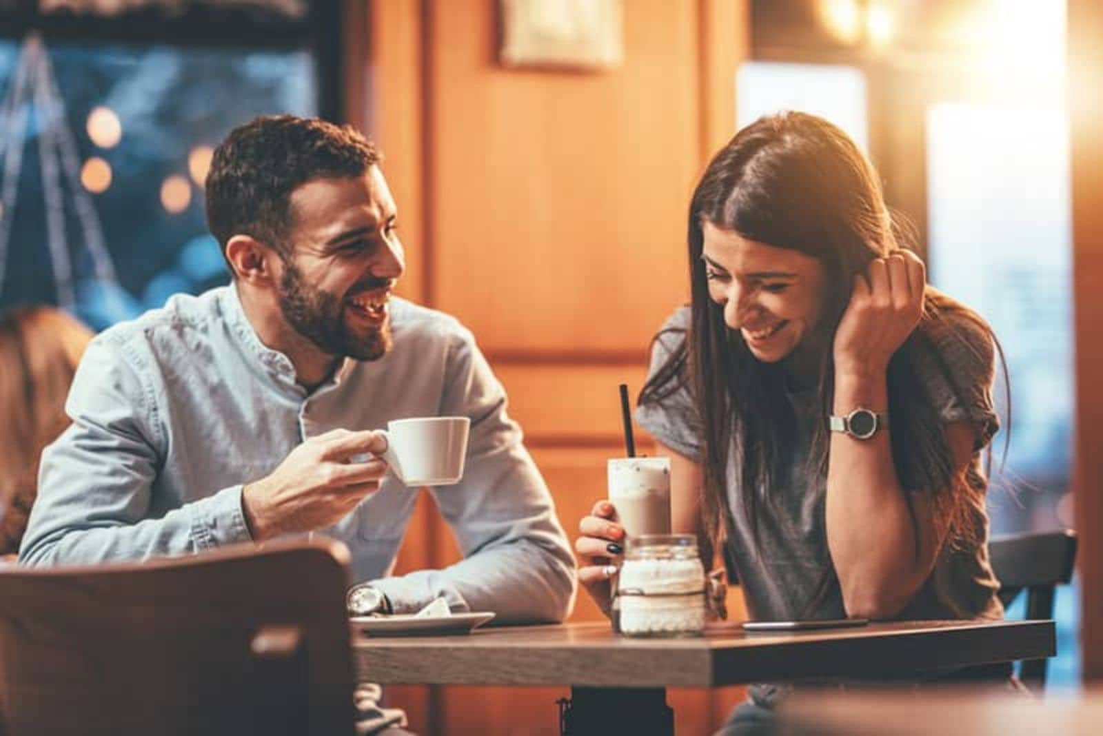 a man and a woman laughing and drinking coffee