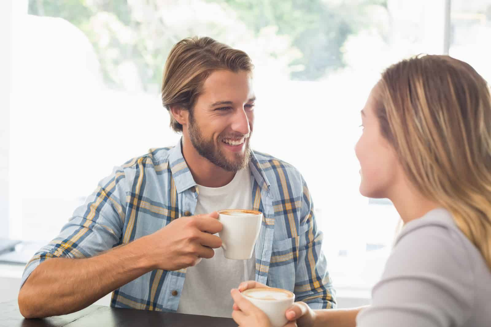 a man and a woman sit drinking coffee and laughing