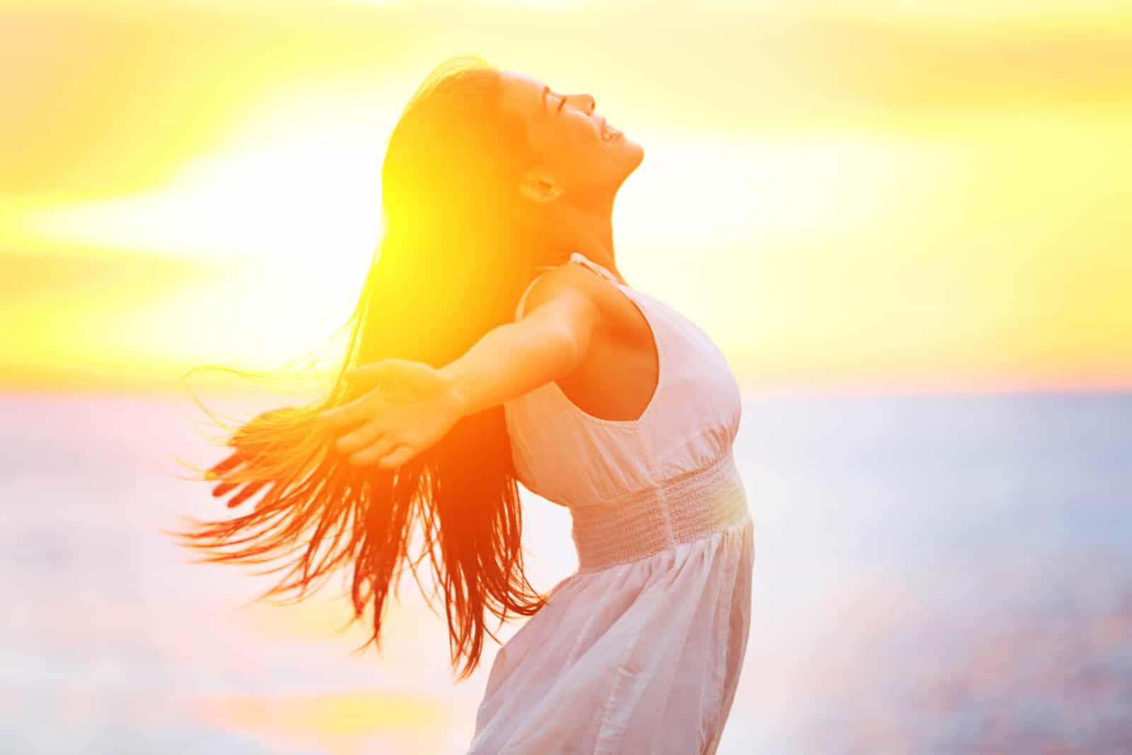 a smiling woman enjoys the sunset