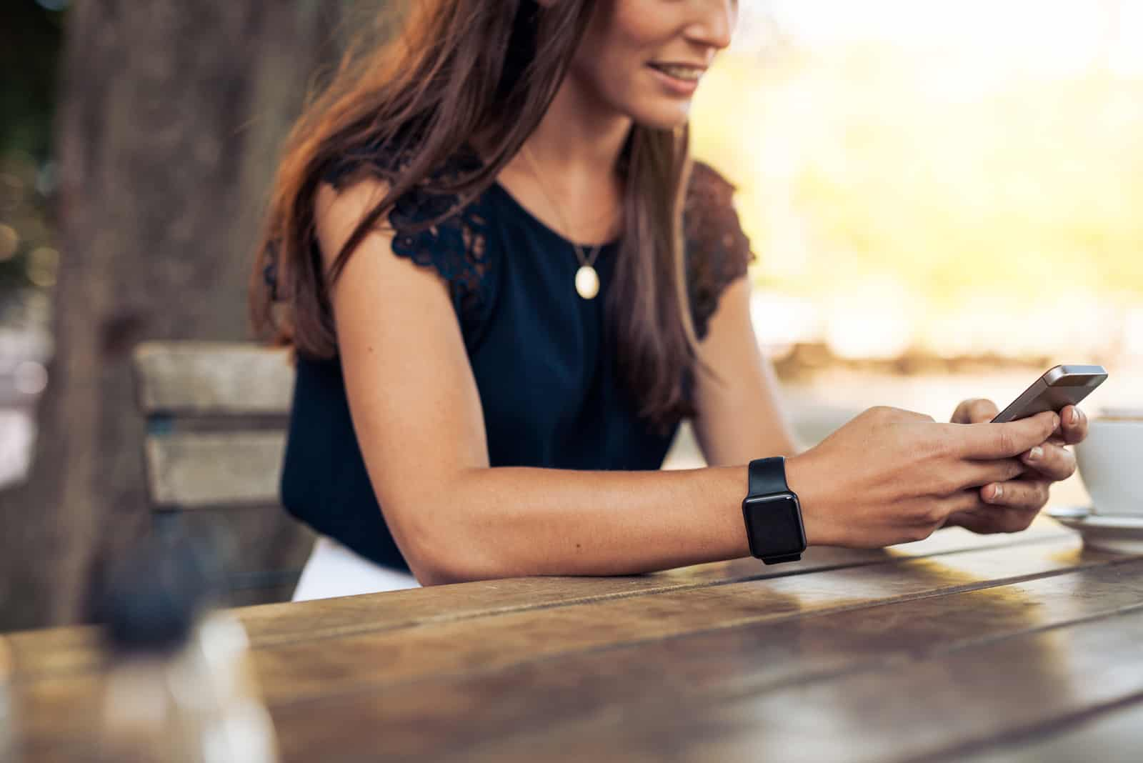 a smiling woman sitting at a table and pressing a phone