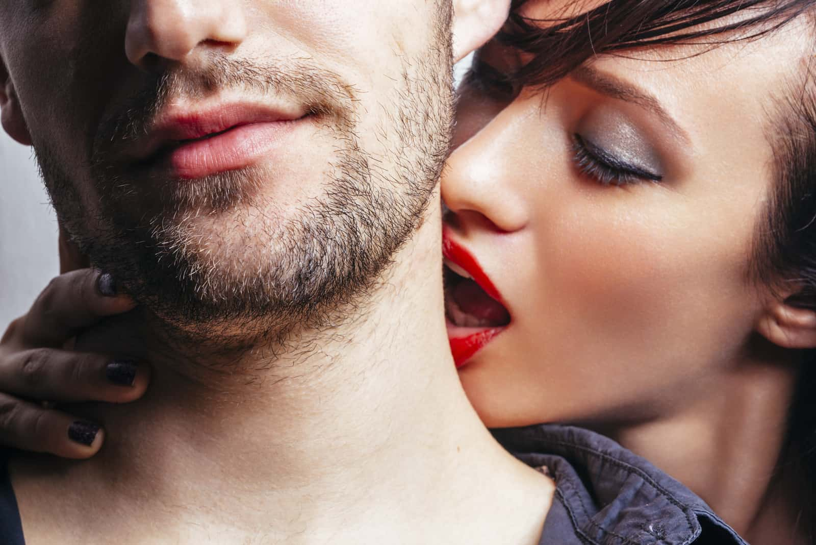 a woman kisses a man on the neck