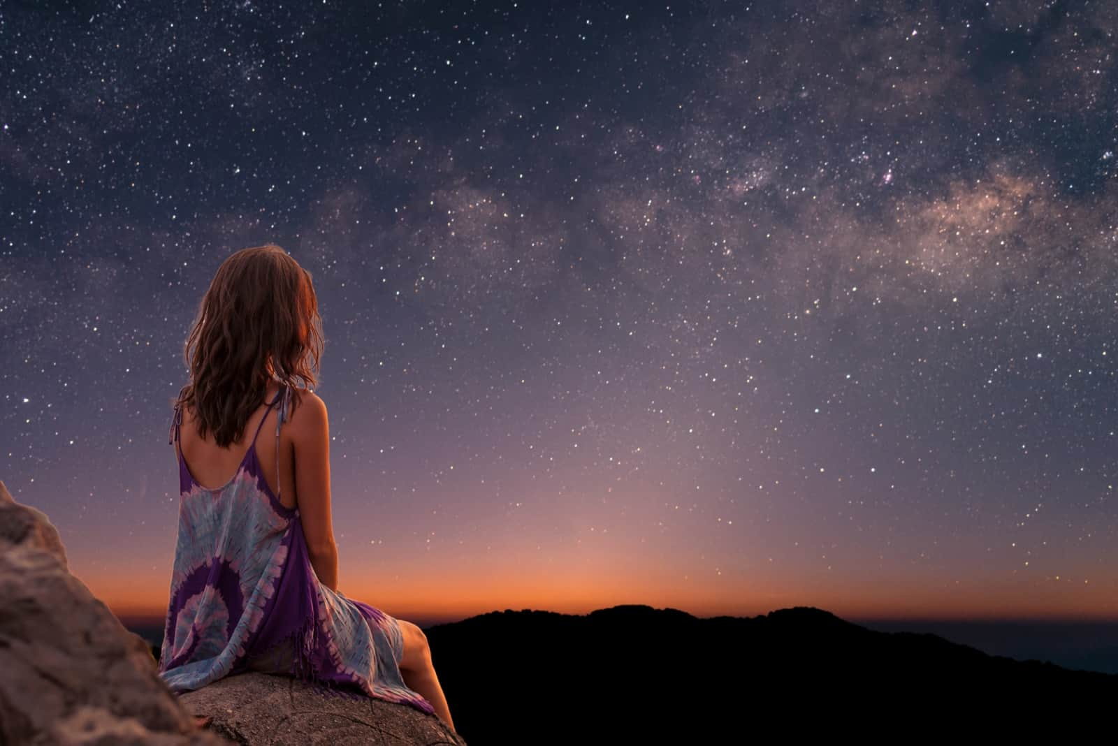a woman sits on a rock and watches the stars in the sky