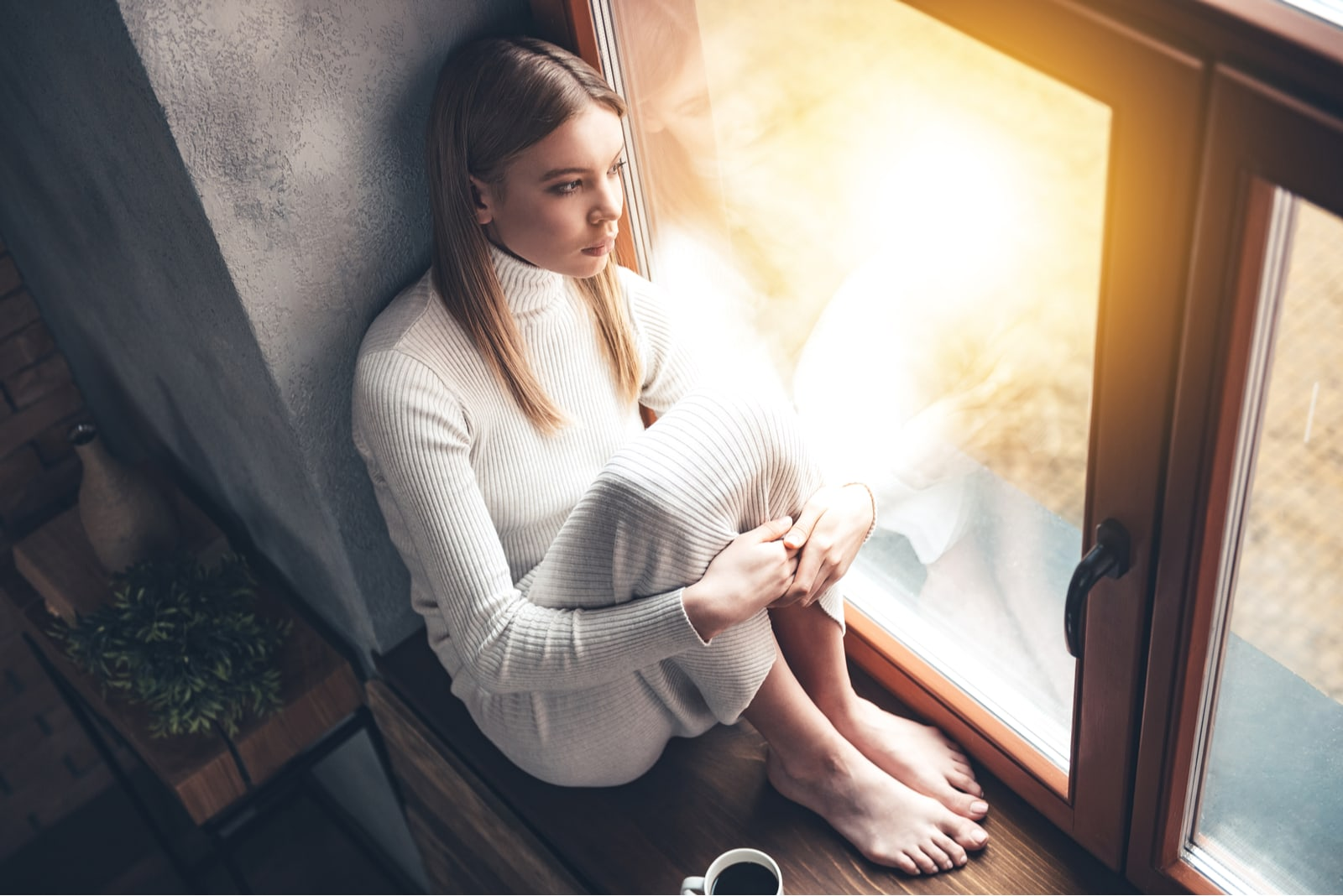 a woman with long brown hair sits by the window and drinks coffee