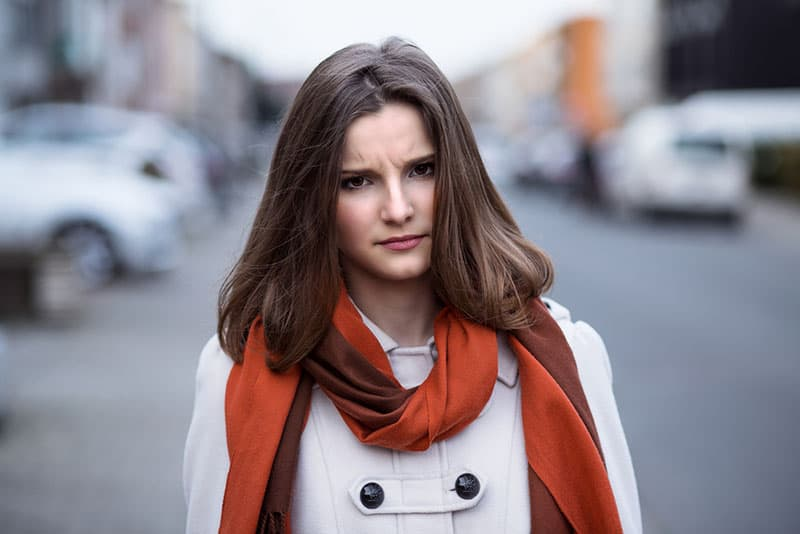 angry and annoyed woman with orange scarf in the street
