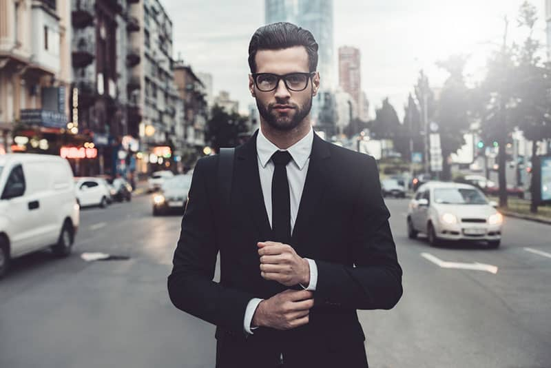 handsome confident business man with glasses standing in the middle of the road