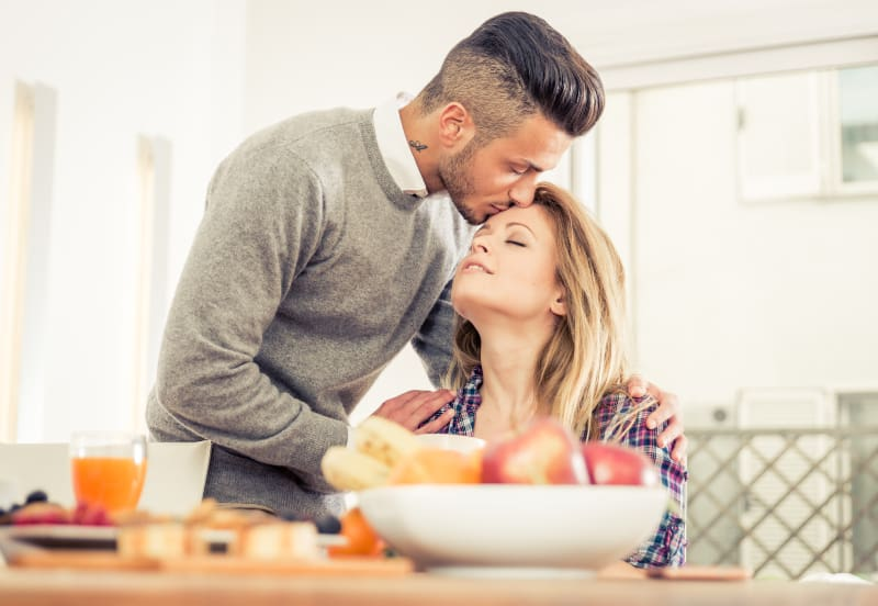 couple having breakfast with wife and kissing her