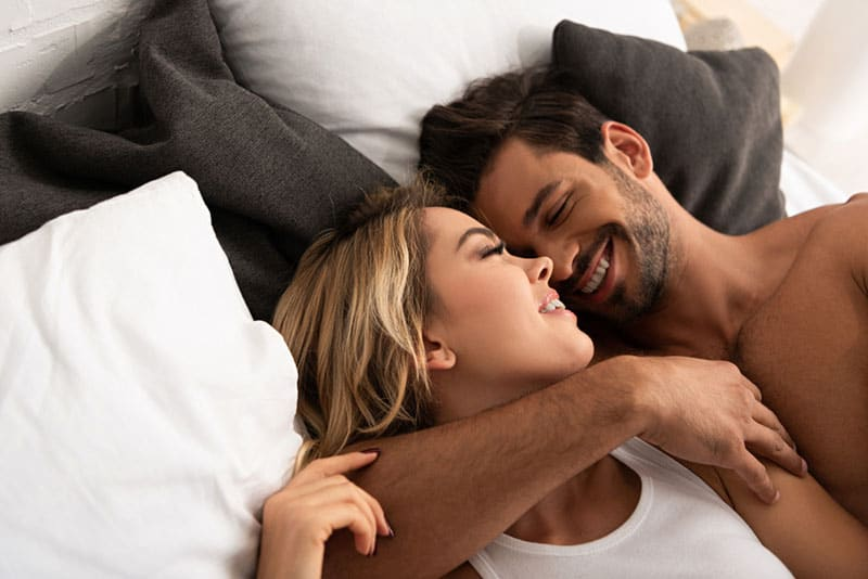 lovely couple hugging and smiling in bed