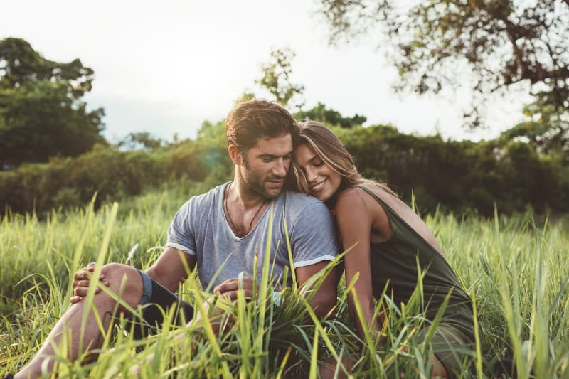 couple hugging while sitting on grass