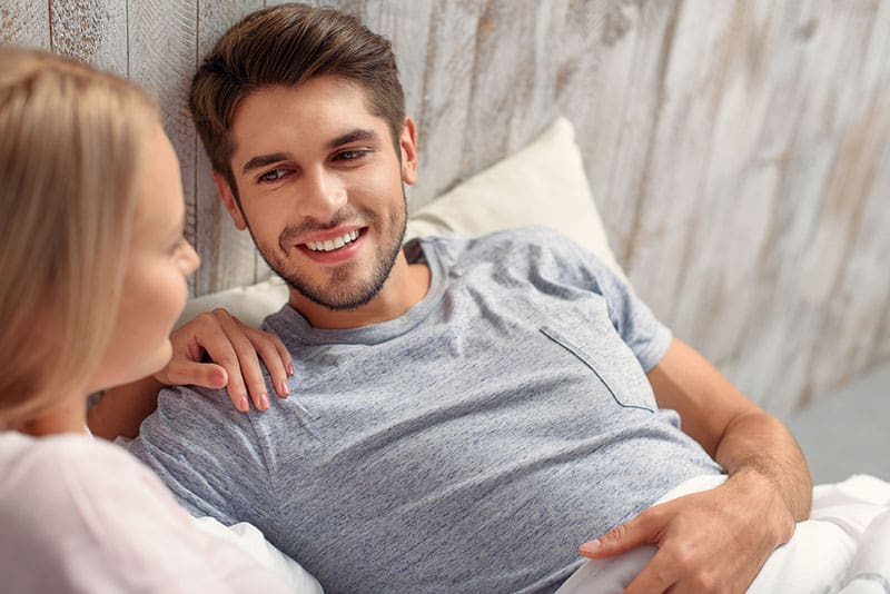 young cute couple talking while laying in bed