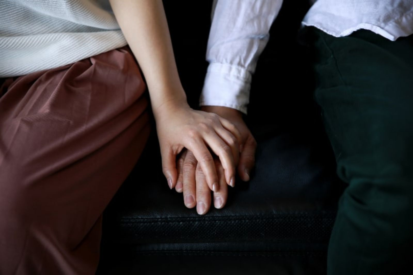 couple on couch holding for hands