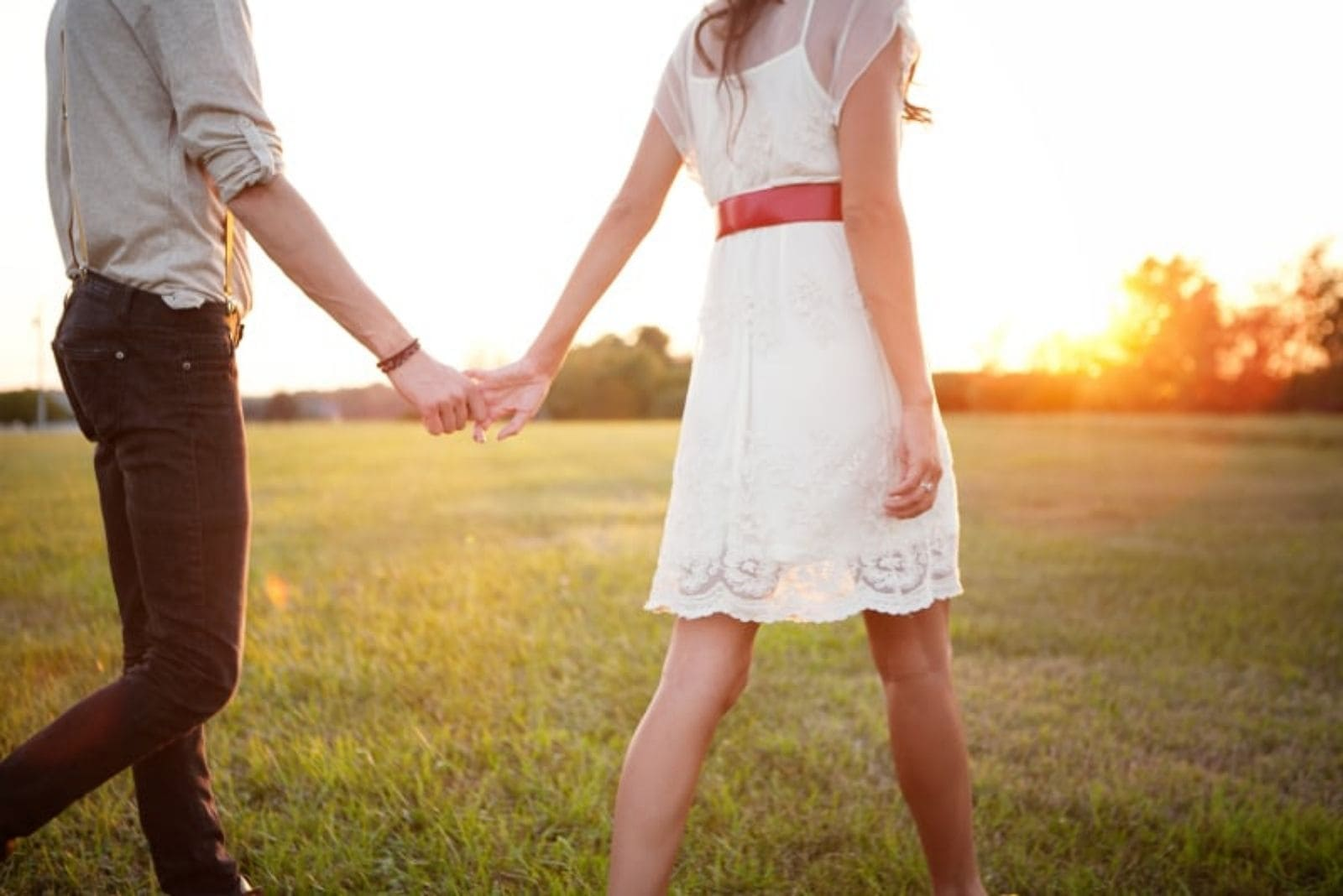 couple walking in the sunkissed field