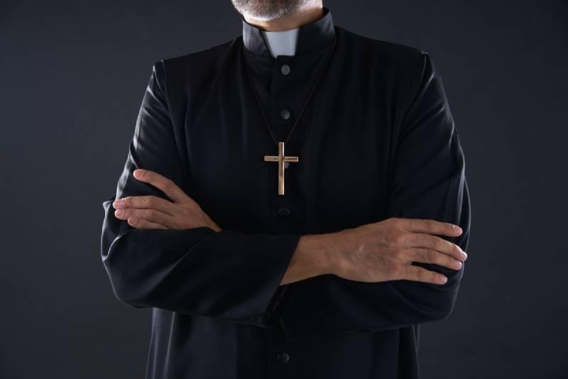 crossed arms priest