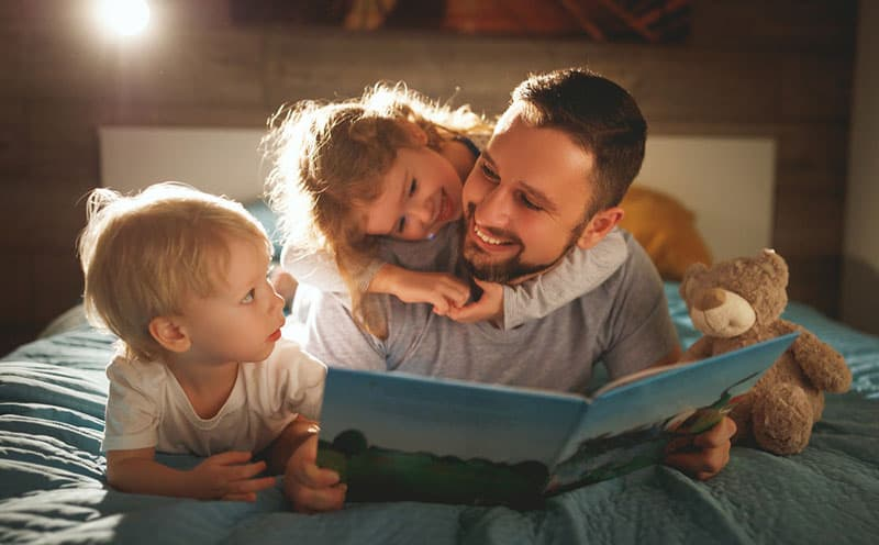 Dad reading a story to his daughter and son in the bed