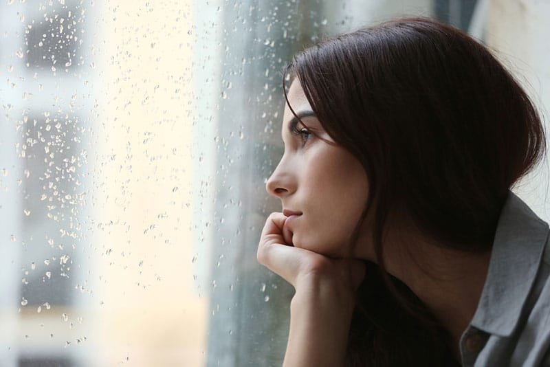 depressed young woman looking through the window while it's rainig outside