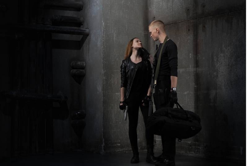 girl and guy in black clothes with guns and bag