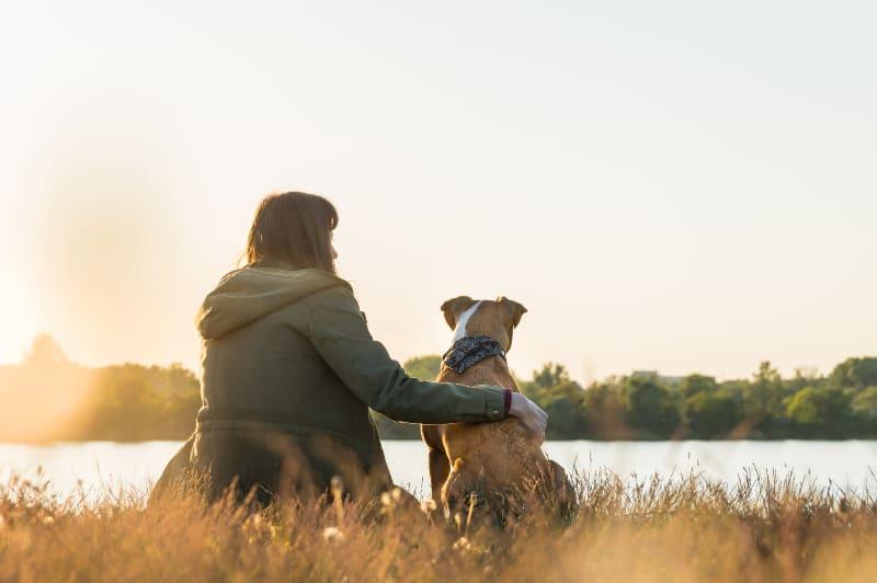 girl with dog sitting near lake