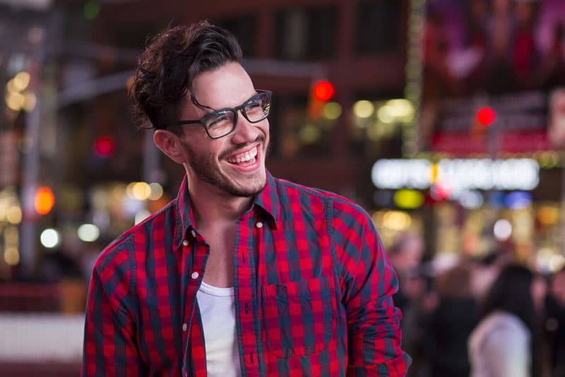 handsome man with glasses laughing in the street