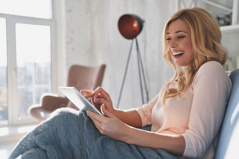 happy young blonde woman laughing at something on the phone