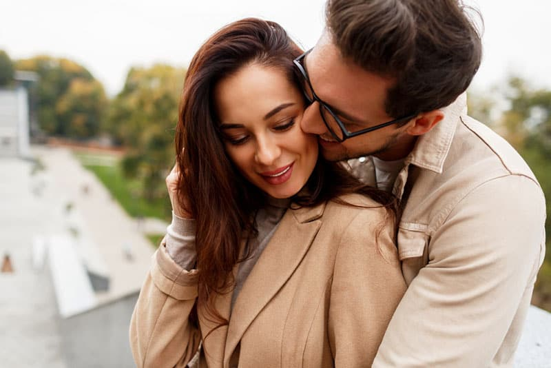 happy young couple outdoors hugging