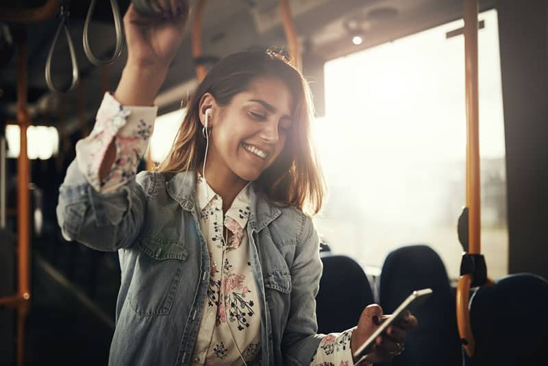 happy coung latino girl smiling on the bus