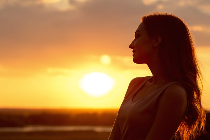 happy strong woman sunkissed on sunset
