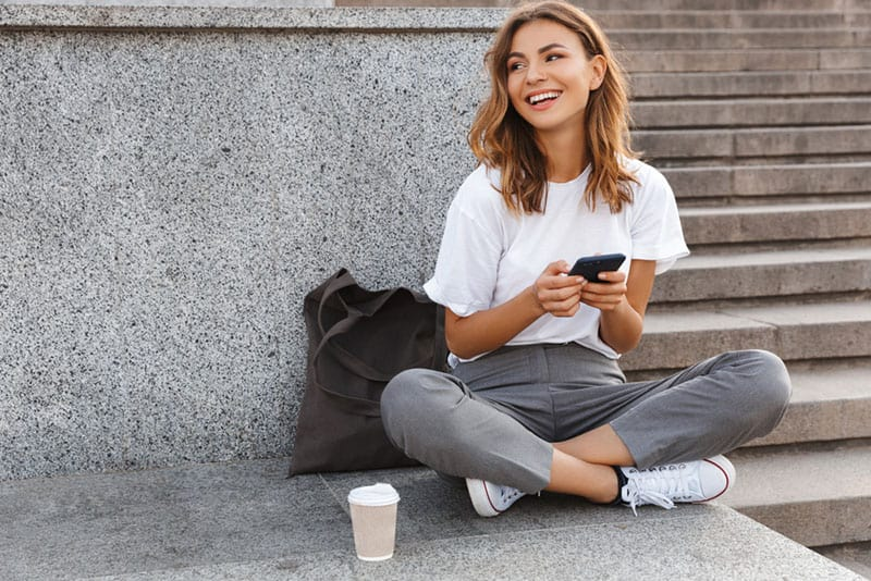 happy young woman smiling and sitting on the floor with her coffee and phone