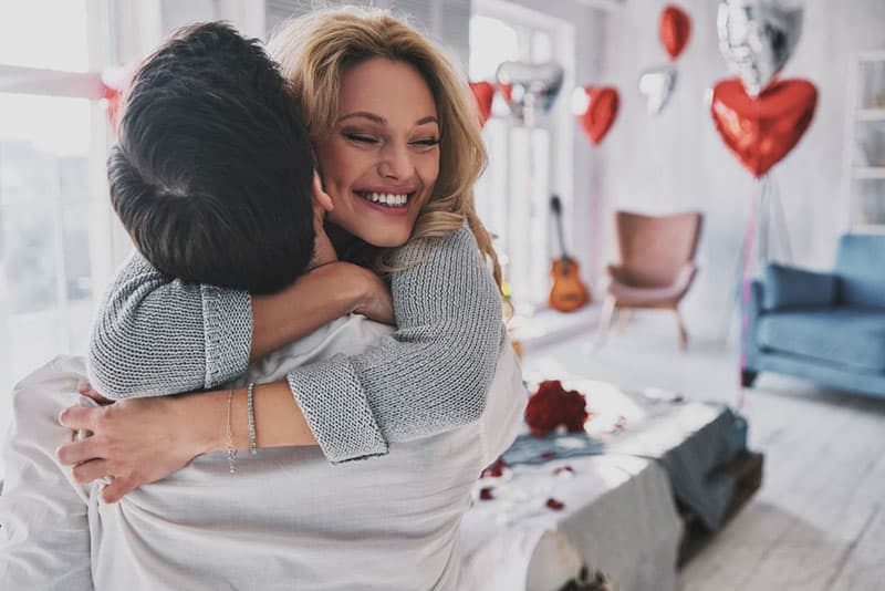 happy young couple hugging in their apartment