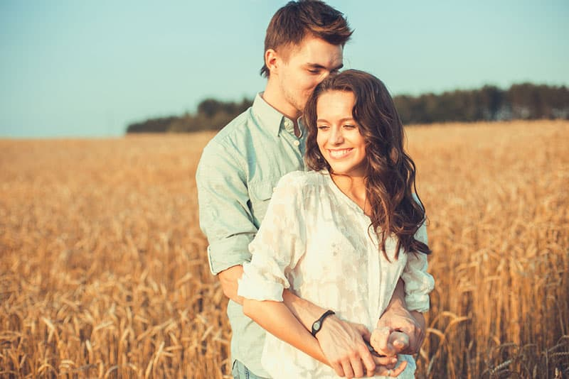 happy young couple standing in the field